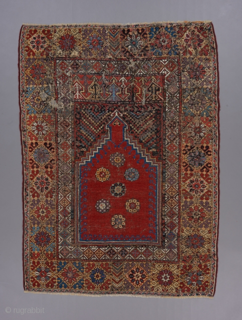 "An Early Mujur prayer rug ca. 1800.  Great colors. Classic design. Beat up with scattered repairs, but still beautiful and desirable. Priced accordingly. 5'7"" x 4'."
