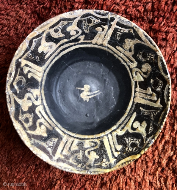 Nishapur Ceramic bowl.  North East Iran, 10th century. Size: 8 x 2.5 inches (20.5cm x 6cm) Stylized bird design in center with Kufic inscription band on rim and sparse, simple decoration  ...
