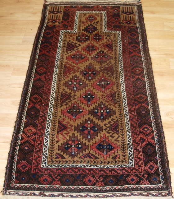 Antique Baluch camel ground prayer rug with interesting Turkmen inspired design.   Circa 1900. Size: 5ft 3in x 2ft 8in (160 x 82cm). The rug is beautifully drawn and has excellent colour, the camel wool  ...