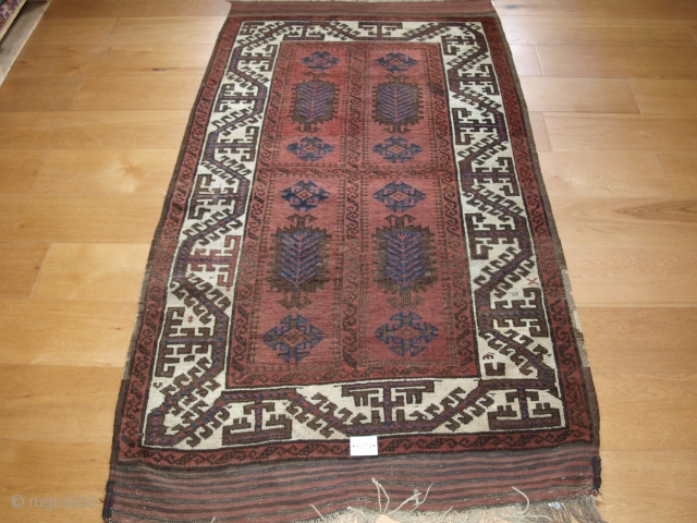 Antique Baluch rug with large scale ivory border and scarce field design. Size: 193 x 104cm, 6ft 4in x 3ft 5in. Note the long kilim ends. Even wear with corrosion to the  ...