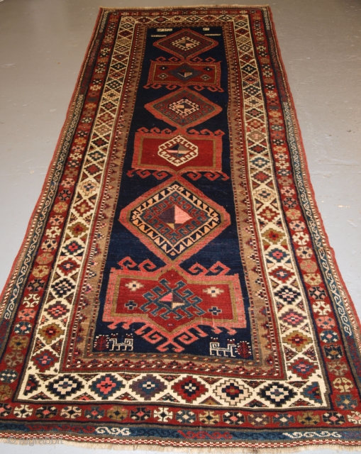 Antique Caucasian Kazak long rug or runner, South West Caucasus. Late 19th century. Size: 10ft 3in x 4ft 0in (312 x 122cm). A pleasing rug with a repeat medallion design on a dark indigo blue  ...