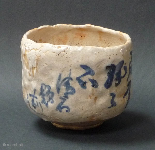 Japanese glazed tea cup (chawan) decorated with a poem and two cormorans in flight.