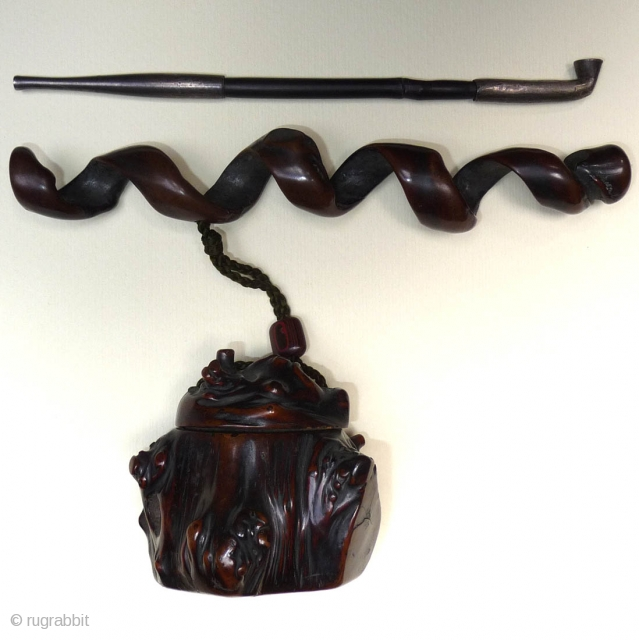 A 19th century Japanese rootwood tobacco box and pipecase with a fine dark patina and the himotoshi ringed in green bone. Pipecase of spiral form. Pipe of bamboo and metal. Ojime of  ...