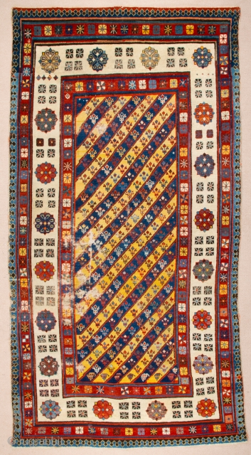 Middle of 19th Century South East Caucasian example, with an yellow and blue field and large rosettes in the white-ground main border, serves as a particularly good illustration of the design affinity  ...