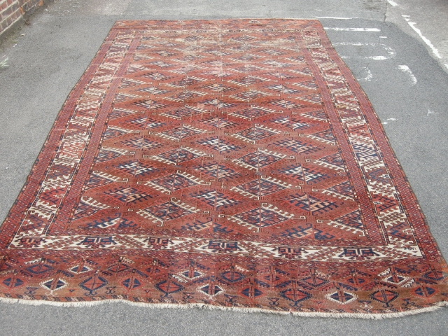 An unusual Antique Turkoman main carpet. Size 11ft 4 x 6ft9. Unusual border design. Not in the best condition wear to one end sides not original.A very attractive carpet.