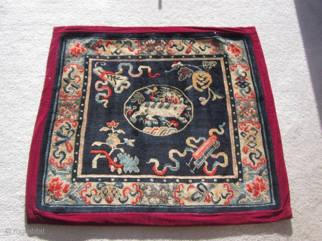 """Tibetan: A pair of large mats, 32 by 36 inches, with prancing and naively drawn central snow lions surrounded by the """"three Fruits"""" and a symbol of scholarly accomplishment. c.1930"""