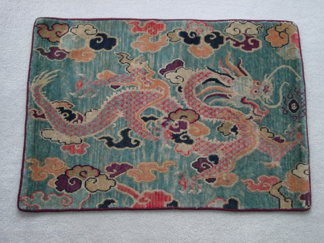 Tibetan dragon mat. Vibrant, folksy dragon in clouds on an abrashed blue ground, c.1920 Nick Wright