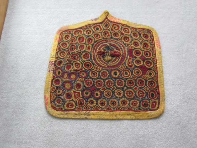 Tibetan: Village-improvised for the local temple. An embroidered throne back chair textile in Gelupga colors and surrounded by yellow ground Chinese silk fragments. In the upper middle of the piece is an  ...