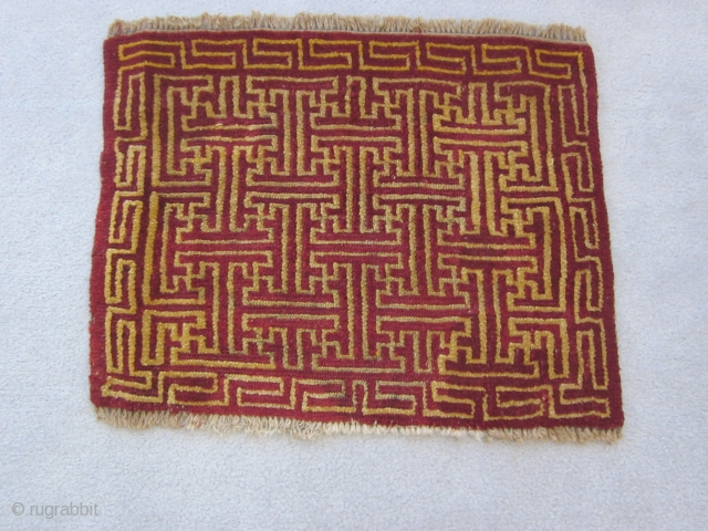 Tibetan mat, 19 by 24 inches, overall running swastika design in red and yellow, small repairs in field, upper 2 inches of border rewoven, early 20th C.