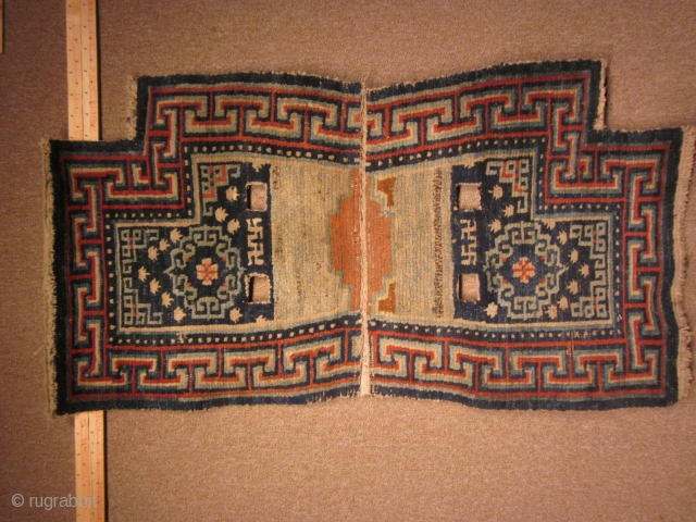 Tibetan: Archaic, and classic notched saddle bottom with asymmetric orange decoration where the two halves join, pre-1900