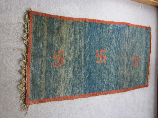 Tibetan khaden, 29 by 55 inches, three red swastikas on abrashed blue ground, natural dyes, pre-1900.