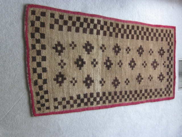 Tibetan khaden, geometric design in browns, with red border. About 3 by 5 ft. c.1930