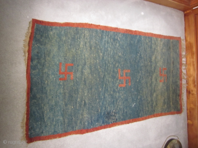 """Tibetan khaden, pre-1900, 2'5"""" by 4'6"""", three eccentric swastikas on an abrashed blue ground, some quality repiling in field"""