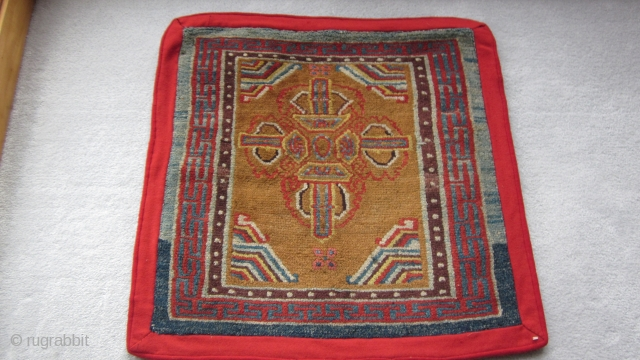 Tibetan sitting mat with eccentric double dorjee, 30 by 30 inches.Village weaving, probably before 1900.