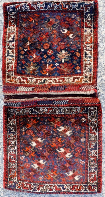 A very freely designed saddlebag woven by Arabic tribes from South West Iran, with a mixture of flower, plants and botehs that contrasts with a more formal border. Very loooooong pile, with  ...