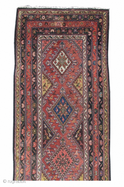 This colorful runner was woven in Persia, in the vicinity of Hamadan. A column of colorful diamonds, articulated with arrowhead motifs, is drawn against a brick red ground. Eight-pointed stars are rendered  ...