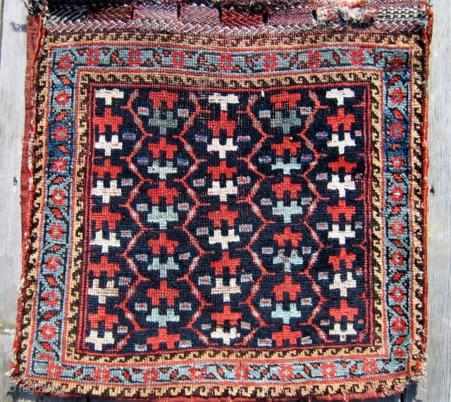 """S.W. Persian Luri Saddle bag (1/2 khordjin) late 19th c.  21"""" x 22"""". An unusual design in this artful Luri bag. Are these stylized flowers or reciprocal human forms filling the deep  ..."""