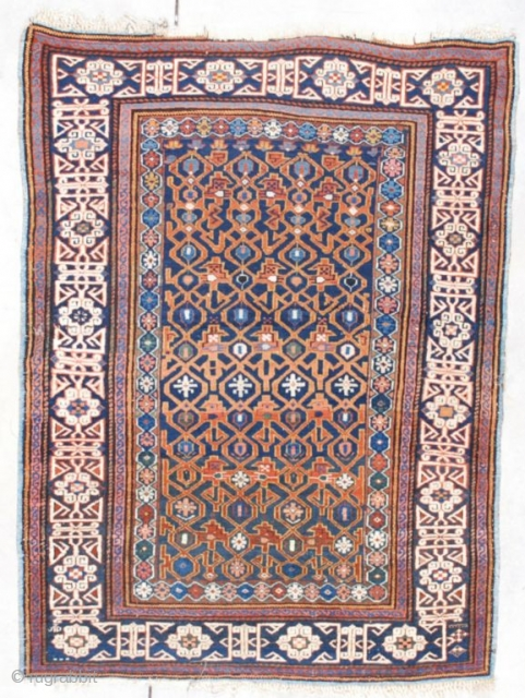 """7554 Kuba This circa 1870 Kuba measures 4'0"""" X 5'3"""" (121 x 161 cm). It has a blue ground with a combination latch hook and trellis design in rusty red on a navy  ..."""