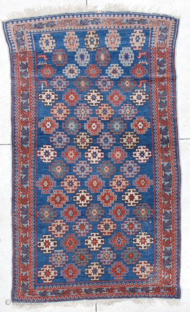 """6471 Antique Kuba This 19th century antique  Kuba measures 3'9"""" X 6'4"""". It has latch hook medallions in red, ivory, yellow, green and pale blue on a medium blue ground with nice  ..."""