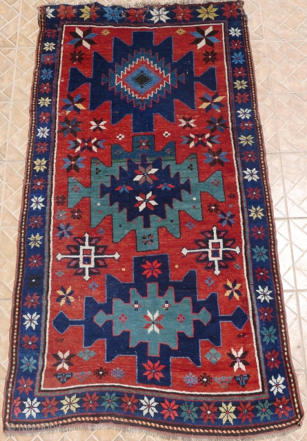 Kazak rug, 7ft x 3.8ft (213 x 117 cm) circa 1910. Attractive sea-green medallions. The madder red ground with scattered flowerheads and cruciform motifs. In general good piled condition.  Small folding  ...