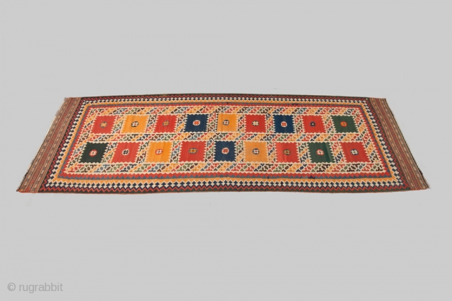 12989. 384x115cm. Circa 1900. Magnificent antique Qashqai kilim runner. All over multicoloured squares with flower heads in the centre are surrounded with multicoloured geometric motifs, framed with a triple border and finished  ...