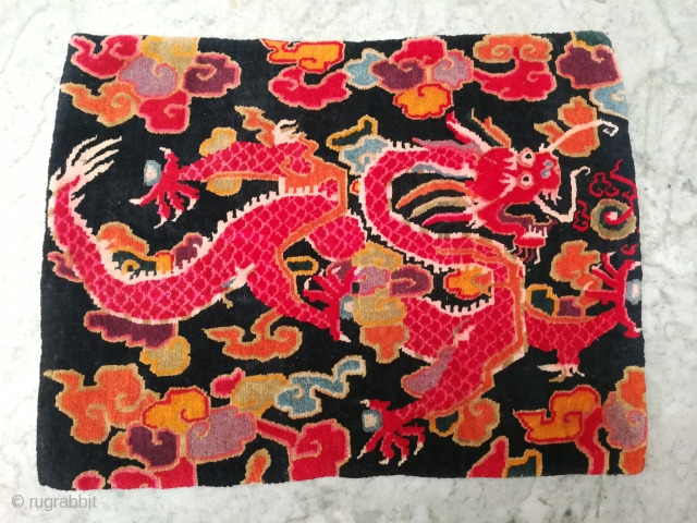 Antique TibetanSingle Rug featuring A Dragon holding Precious jewels surrounded by multi colour clouds in dark blue indigo background.it's not black . Good age and very good quality..condition too.