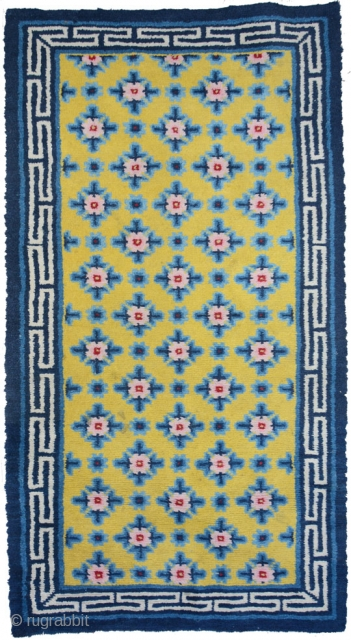 Very appealing medium sized Chinese carpet, most likely from the Ningxia area. The large 'Running T' main boarder anchors a richly saturated yellow center field with superimposed flower like rosette's set over  ...