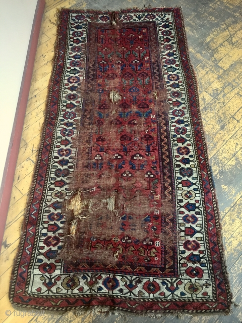 Antique northwest Persian or Kurdish rug or what remains of a rug. Has lovely old natural colors and charming drawing. I like the little border elements that look like houses. Lots of  ...