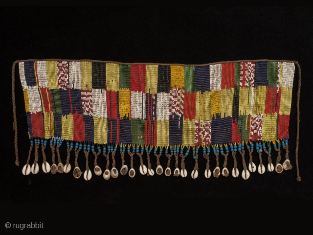 """Pikuran (cache-sex), Bana Guili people, Mandara Mountains, Cameroon. Seed beads, cotton string, cowrie shells, 21"""" (53.3 cm) wide by 9"""" (22.8 cm) high Mid 20th century. These colorful cache-sex were worn for celebrations, rituals and rites of  ..."""