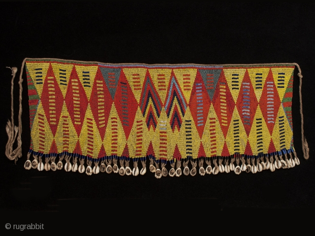 "Pikuran (cache-sex), Bana Guili people, Mandara Mountains, Cameroon. Seed beads, cotton string, cowrie shells, 21"" (53.3 cm) wide by 9"" (22.8 cm) high Mid 20th century. These colorful cache-sex were worn for  ..."