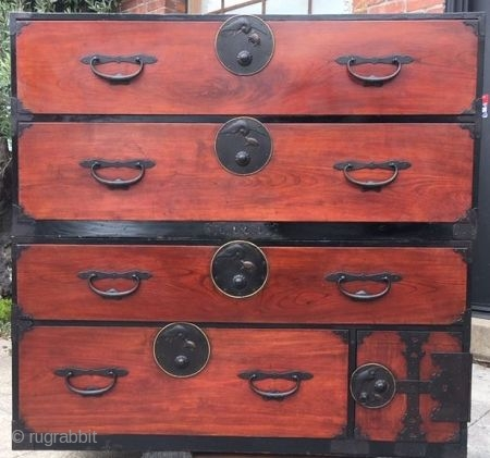 Japanese Antique 2-Section Nihon Matsu Isho Tansu  A Nihon Matsu tansu with beautiful reddish brown lacquered keyaki wood front face with hinoki (cypress) wood drawers. The round lock plates on each drawer feature  ...