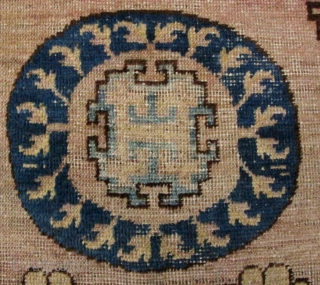 Chinese: Antique Xinjiang carpet. This piece has alternating wool and cotton weft threads, with cotton warp and wool pile. There are three moon flower medallions with simple key fret and flower  ...