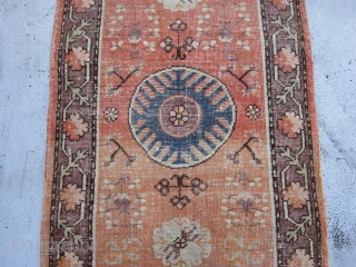 Small Khotan Runner circa 1920's , 6.8 x 2.5 A round,mid blue medallion centers a salmon field ornamented with fruits,stylized flowers,rosettes and leafy quatrefoils.The mauve-brown border of rosettes and stiff vines is also  ...