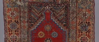 """An Early Mujur prayer rug ca. 1800.  Great colors. Classic design. Beat up with scattered repairs, but still beautiful and desirable. Priced accordingly. 5'7"""" x 4'."""