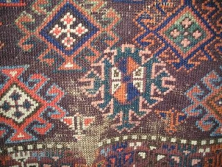small symmetrically knotted Baluch rug with fantastic color (including three greens, several blues, pink, orange, purple and chocolate brown) and a simple border with geometricized flowering plants. 84x132 cm(33\'\'x52\'\' inches)