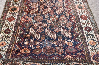 An antique Shekarlu Qasgai rug of unusual small size. Typical design, with a riot of colourful filler elements framed by sunburst borders. A good tribal rug this, with fine silky wool and  ...