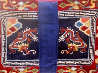 Antique butterfly-shaped Tibetan saddle cover or rug, dragons and mountains on a deep blue field in a spare design usually associated with earlier examples.  Early 20th Century. Traditional red edging (faded)  ...