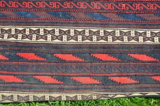 "Baluch flat woven khorjin. 1st 1/2 20th C. 25"" X 60-1/2"". Wool. Clear bright colors (no color run or fading). Faces with geometric weft substitution  designs. Plainwoven white back (stain at  ..."