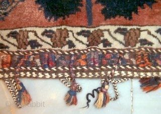 AFSHAR TRIBAL TENT BAG which is rare because of its inscription in the field. The field is dominated by a central tree with songbirds at each lower side. At the top there  ...