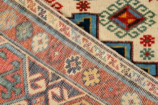 Caucasian Kuba Rug The white field contains three Lesghi stars, alternately in shades of blue and red, which are surrounded by a multitude of small hooked diamonds, stars, crosses and blossoms. The  ...