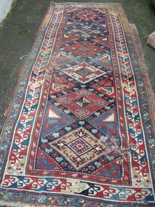 a very beautiful but badly damaged caucasian rug mid 19th. Approx 9ft x 3ft6. great colours and design in pile but with many problems still a wonderful old rug.