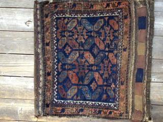 Early Antique Baluch Bag. Complete, with good colors including outstanding blues. Archaic and unusual design. Low pile with some oxidation and some fraying on sides and ends. Nice striped kilim open back.  ...