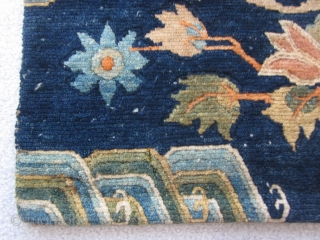 Tibetan sitting mat with phoenix in central rondel,fowers and wave border, about 2 by 2 ft, c.1930