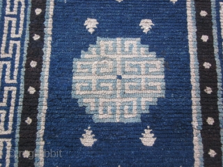"Tibetan: Vintage khaden, 2'3"" by 4'6"", with latch hook central medallion in light blue and frog's feet on a saturated indigo ground, before 1900. Some scattered re-piling."