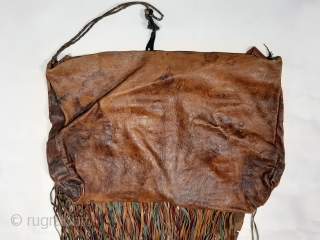 "Tuareg leather womans travel bag (""aghrig""), with hand worked and dyed leather, probably goat skin. Intricate leather work with check pattern cut into dyed skin and embroidered thread patterns. The green dyed  ..."