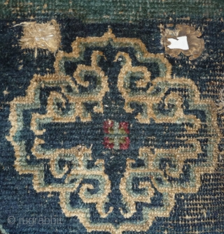 great ancient tibetan saddle with narrow white border, the medalions display an early design. Tibet early 19th century or before.