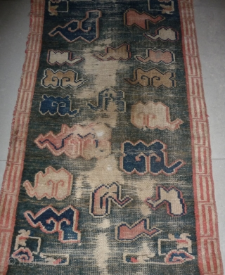 all about clouds. an early 20th century tibetan popart rug with an abrashed green sky background. damage but a funny unique piece; note the integration of a cloud design in the traditional  ...
