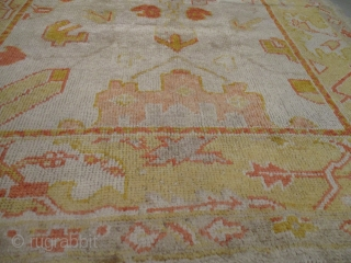 """This Oushak rug measures 4'5"""" X 6'0"""". It has a cream colored angora wool field containing a very confused asymmetric motif in bittersweet, yellow, grey and peach. The outer border has leafs,  ..."""