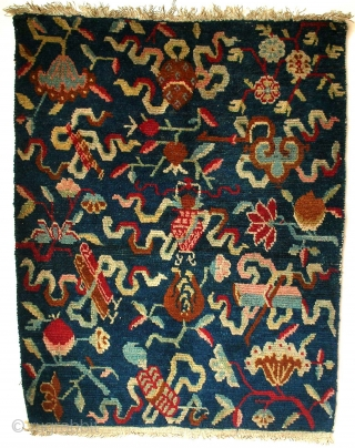 Jabuye, Tibet, late 19th century, cm 77x60. This pillow rug (jabuye) is quite an interesting one, for its overall design is a merry riot of motifs. This relates to the fact that  ...