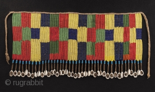 """Pikuran (cache-sexe, Bana Guili people, Mandara Mountains, Cameroon. Seed beads, cotton string, cowrie shells. 16.25"""" (41.2 cm) wide by 8.25"""" (21 cm) high. With base 20.75"""" (52.7 cm) wide by 12.25"""" (31  ..."""